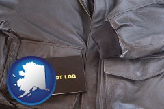 alaska map icon and an leather aviator jacket and pilot log book