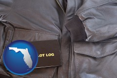 florida map icon and an leather aviator jacket and pilot log book