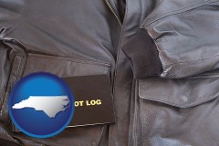 north-carolina map icon and an leather aviator jacket and pilot log book