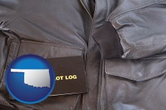 oklahoma map icon and an leather aviator jacket and pilot log book
