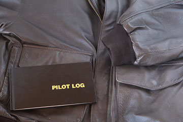 an leather aviator jacket and pilot log book